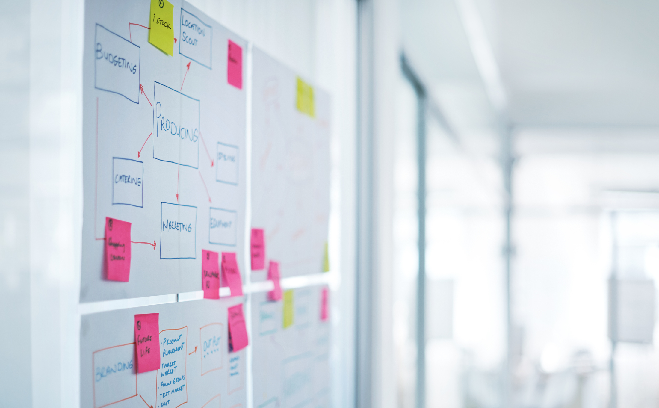 Shot of a bunch sticky notes and plans on a glass wall