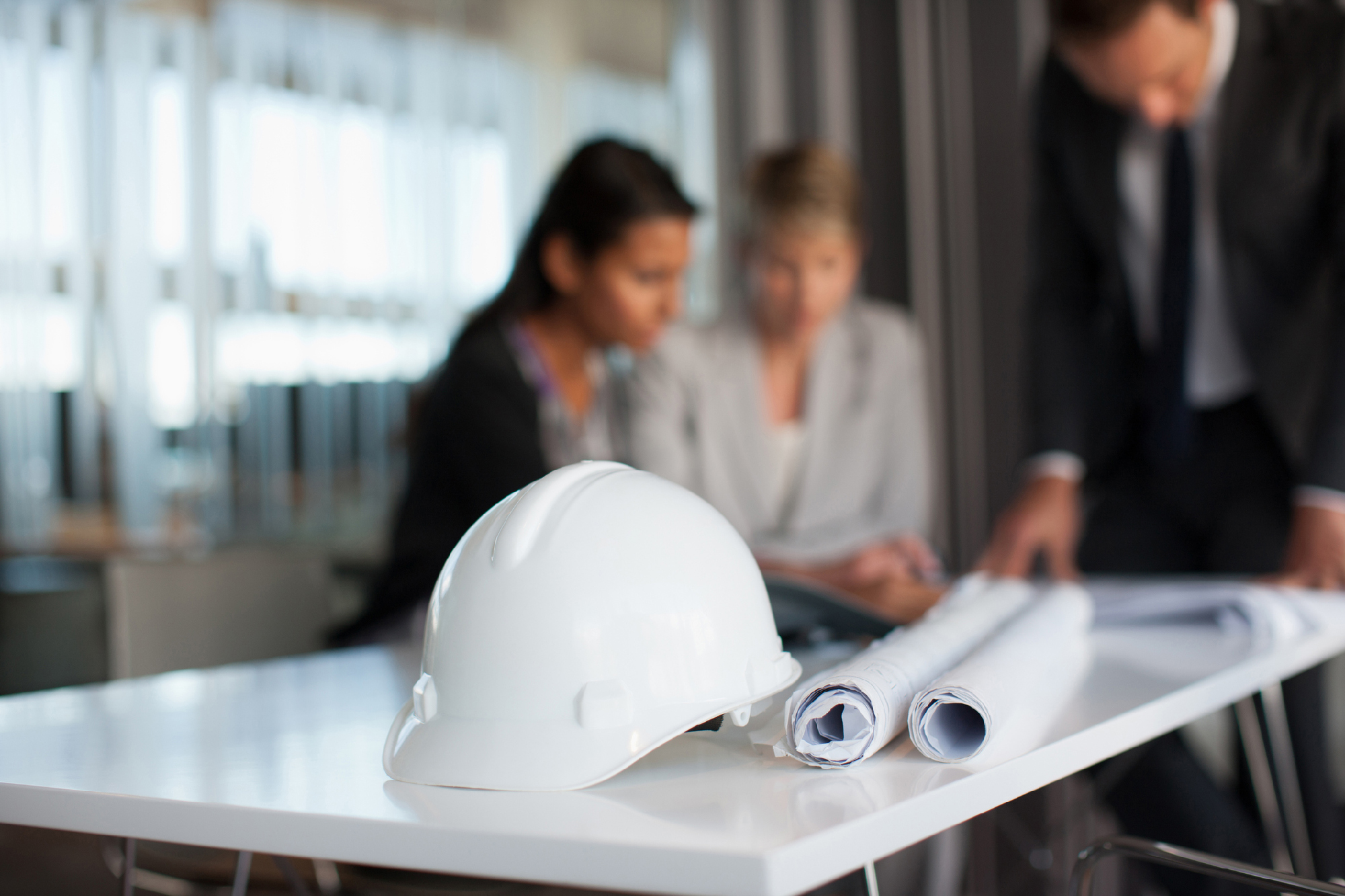 Hard hat in focus with Business people reviewing blueprints in conference room