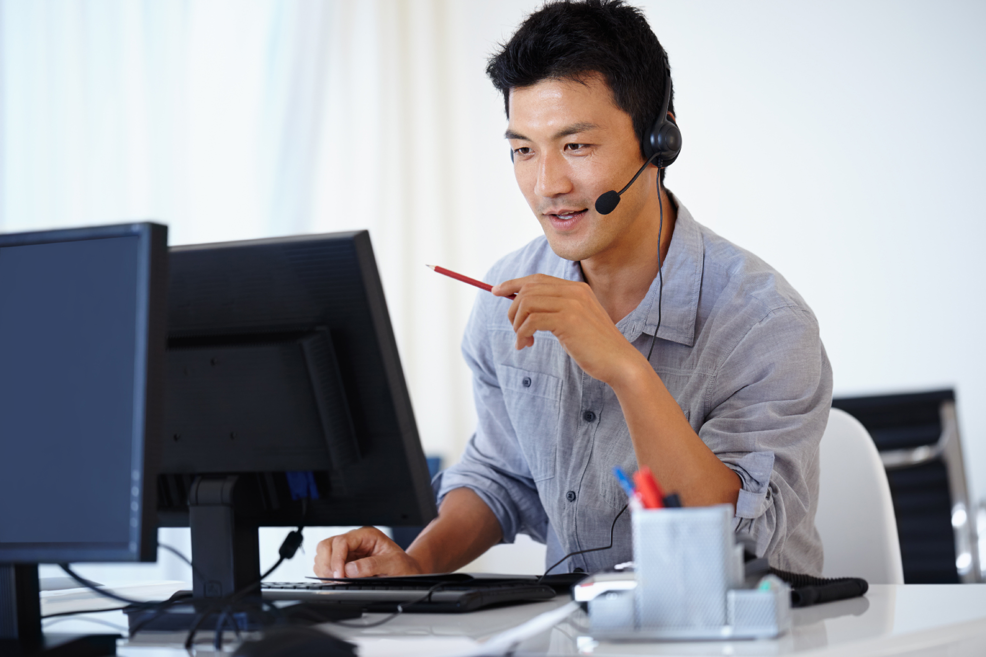 Asian man using a computer and talking on a headset